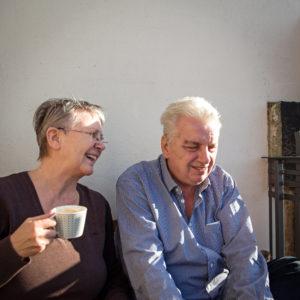 älteres Paar trinkt Kaffee aus einer Bank